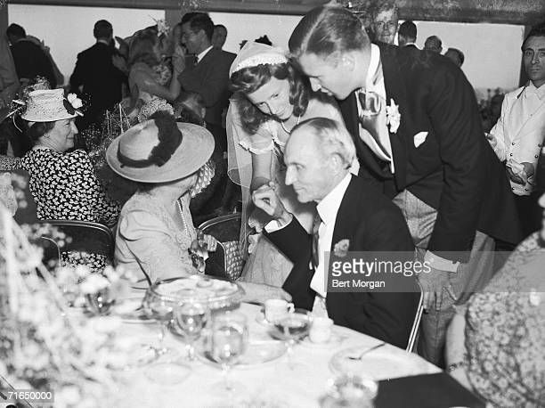 American innovator and industrialist Henry Ford sits and listens as his grandson Henry Ford II and his new wife Anne McDonnell Ford talk to him and...
