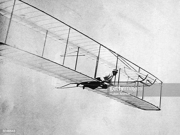 American inventor and aviator Wilbur Wright flies a glider biplane which he designed with his brother Orville in Kitty Hawk, North Carolina.