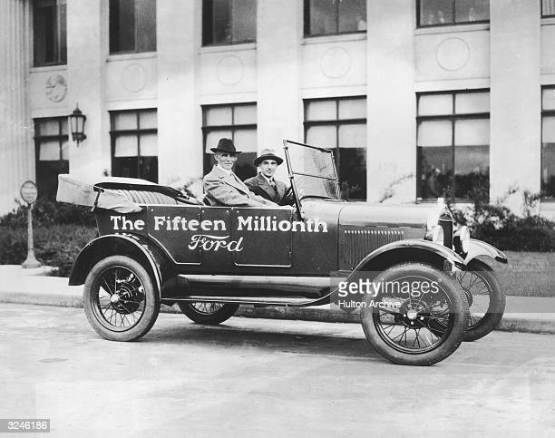 American inventor and industrialist Henry Ford and his son automobile executive Edsel Ford sit in 'The Fifteenth Millionth Ford'