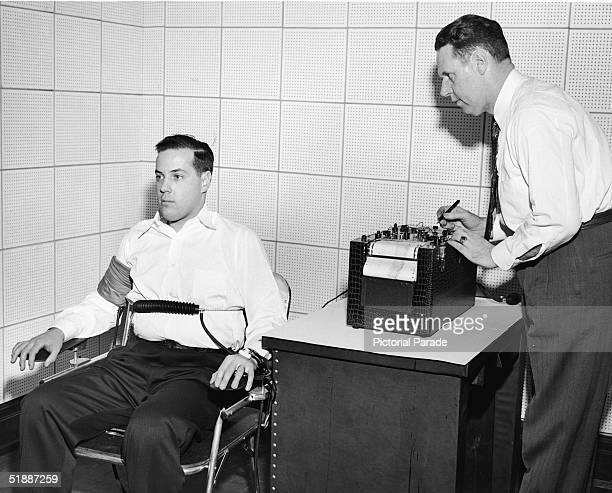 American inventor John Larson demonstrates the operation of a polygraph or 'lie detector' at Northwestern University Evanston Illinois 1930s Such a...