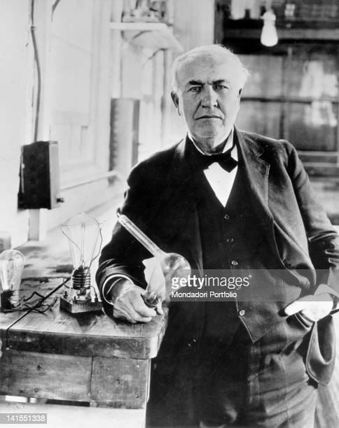 American inventor Thomas Alva Edison holding a light bulb in his laboratory Menlo Park 1910s