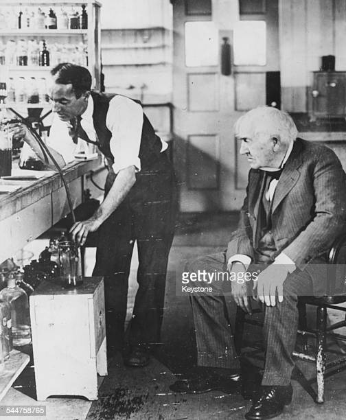 American inventor Thomas Edison watching his assistant George A Hart performing an experiment on rubber in their laboratory West Orange New Jersey...