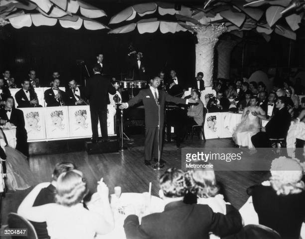 American jazz and pop singer Billy Eckstine performs with an orchestra at the Copacabana nightclub New York City Eckstine sings at the microphone...