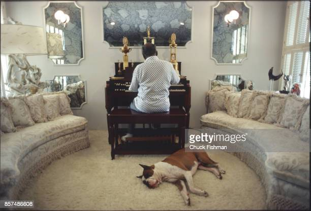 American Jazz and Swing musician Count Basie plays the organ in his living room as his bulldog Graf lies on the carpeted floor Freeport Bahamas March...