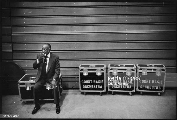 American Jazz and Swing musician Count Basie smokes a cigar as he sits on a trunk backstage in a college gymnasium before a performace August 1978