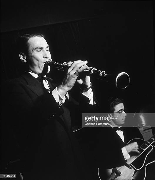 American jazz clarinetist and bandleader Artie Shaw performs with his band at the Hotel Lincoln New York City A guitarist plays next to him Shaw's...