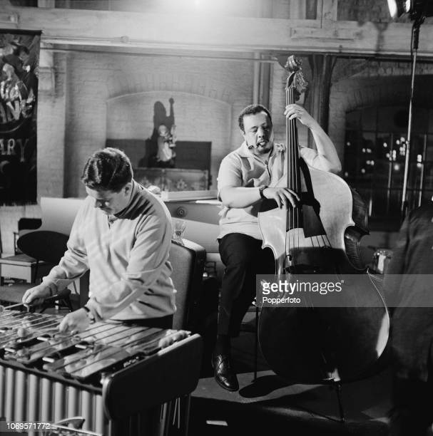 American jazz double bassist Charles Mingus pictured performing with English jazz musician Tubby Hayes during a recording for the film 'All Night...