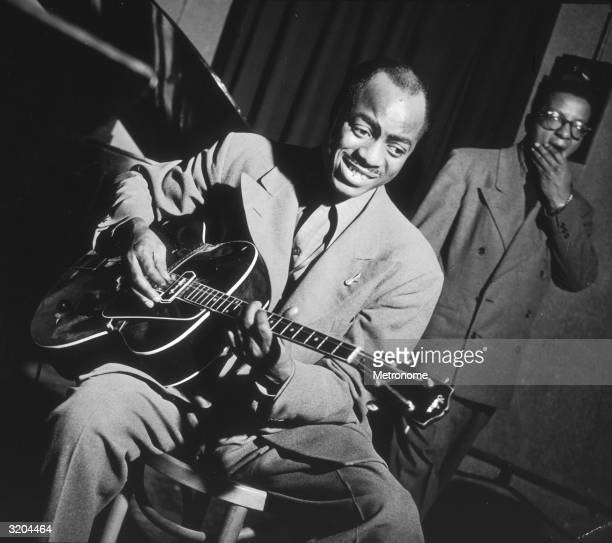 American jazz electric guitarist Tiny Grimes sits and plays guitar while composer and pianist Billy Strayhorn stands behind him at a Metronome...