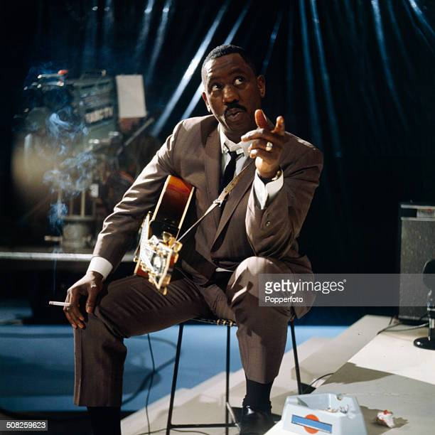 American jazz guitarist Wes Montgomery posed smoking a cigarette with a Gibson L5 semi acoustic guitar in a television studio during a recording for...