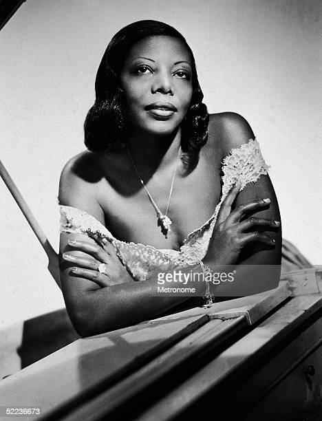 American jazz music great pianist and composer Mary Lou Williams leans on a grand piano with her arms folded across her chest and wears an...