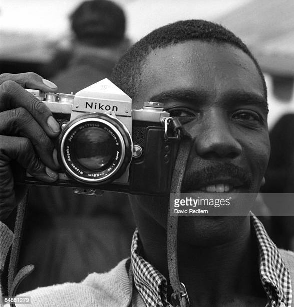 American jazz musician Jimmy Smith posed holding his Nikon camera at Juan-les-Pins in France in 1963.