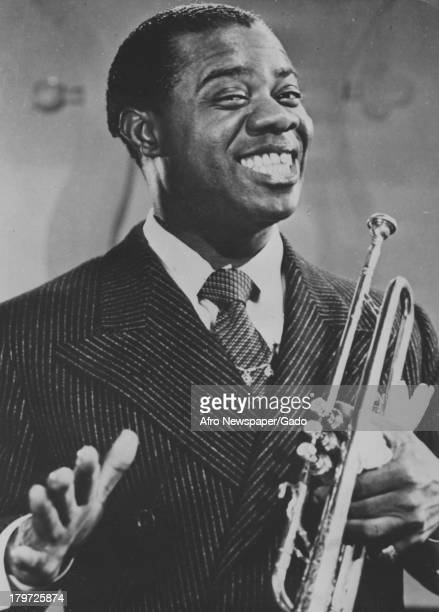 American jazz musician Louis Armstrong poses with his trumpet and a huge smile 1937