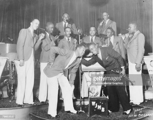 American jazz musician Louis Armstrong smiles as he poses on stage with a band for the WMSB radio station in New Orleans, Louisiana, 1920s.