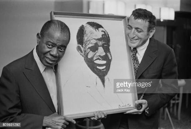 American jazz musician Louis Armstrong with a portrait of himself which was drawn by American singer Tony Bennett at the Savoy Hotel London 29th...
