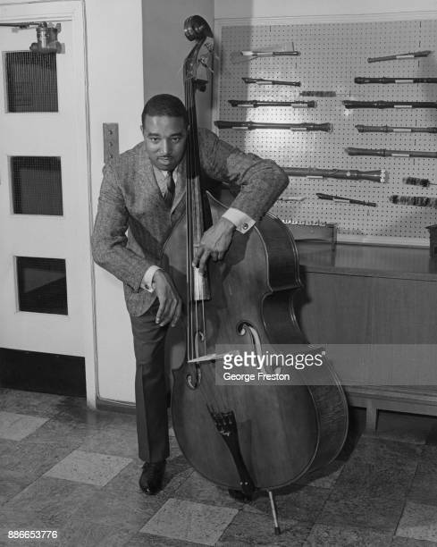 American jazz musician Ray Brown on his double bass in front of a collection of recorders 10th April 1964
