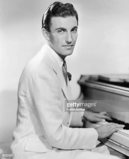 American jazz pianist and bandleader Eddy Duchin playing the piano and looking over his shoulder in a promotional portrait for his film debut in...