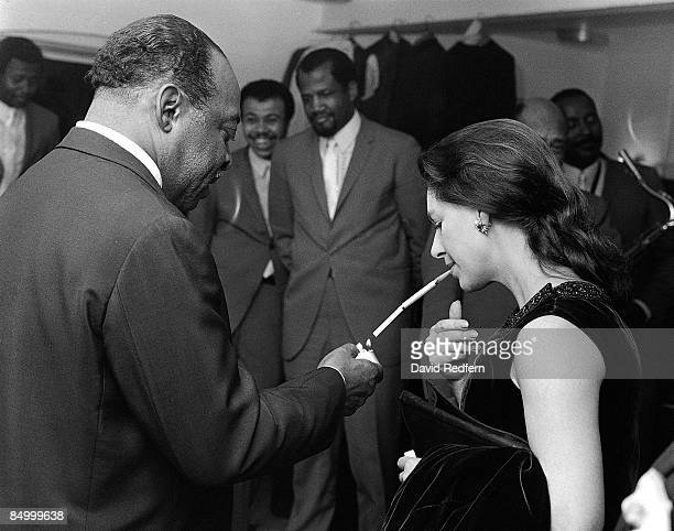 American jazz pianist and composer Count Basie lights a cigarette in its holder for Princess Margaret, Countess of Snowdon backstage during the...