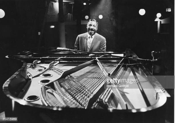 American jazz pianist and composer Erroll Garner sits behind the keys of an open grand piano and smiles over the soundboard 1960s
