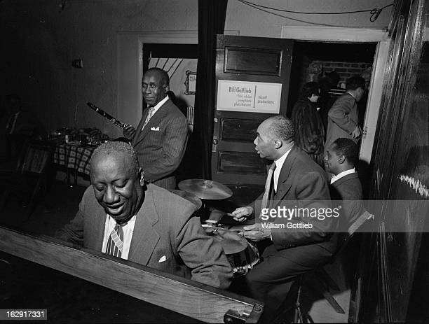American jazz pianist and composer James P Johnson performing with drummer Freddie Moore and clarinettist Fess Williams at an office party given by...