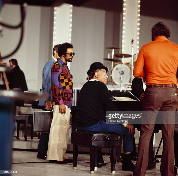 American jazz pianist, composer and bandleader Duke Ellington seated at a piano with Quincy Jones on stage during recording of the 'Duke...