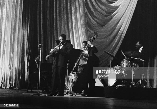 American jazz saxophononist composer and musician John Coltrane performs live on stage with from left pianist McCoy Tyner bassist Reggie Workman and...