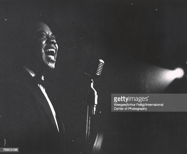 American jazz singer and trumpeter Louis Armstrong performs on stage illuminated by a single spotlight 1940s ot 1950s Photo by Weegee/International...