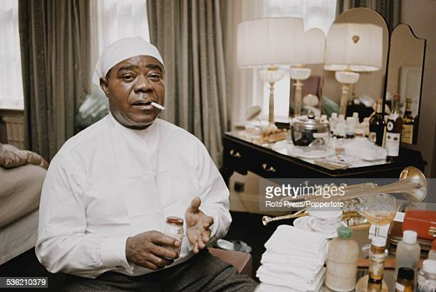 American jazz trumpet player and singer Louis Armstrong pictured smoking a cigarette at a dressing table in a hotel bedroom in 1963 Armstrong's...