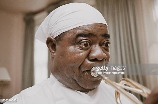 American jazz trumpet player and singer Louis Armstrong pictured playing his trumpet in a hotel bedroom in 1963 Armstrong wears a handkerchief over...