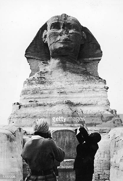 American jazz trumpeter and bandleader Louis Armstrong plays trumpet in front of the Sphinx of Ghiza Egypt as a native man takes his picture 1950s