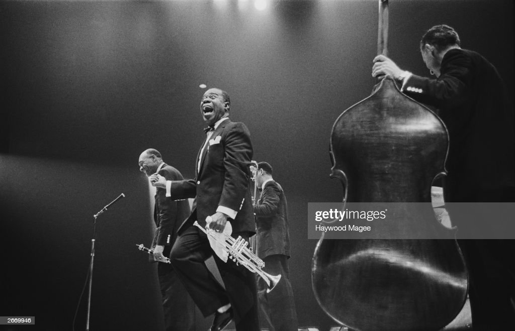 American jazz trumpeter and bandleader Louis 'Satchmo' Armstrong (1900 - 1971), shouts after clarinettist Edmund Hall's solo, on stage during the band's British tour, May 19, 1956. An unidentified bassist stands in the foreground.