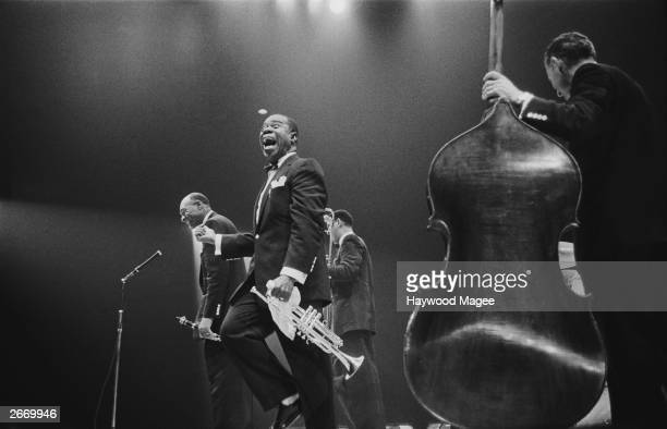 American jazz trumpeter and bandleader Louis 'Satchmo' Armstrong shouts after clarinettist Edmund Hall's solo on stage during the band's British tour...