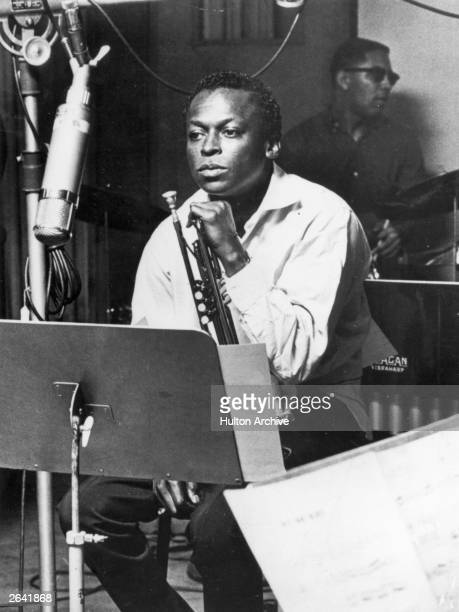 American jazz trumpeter and composer Miles Davis sits with his instrument during a studio recording session October 1959