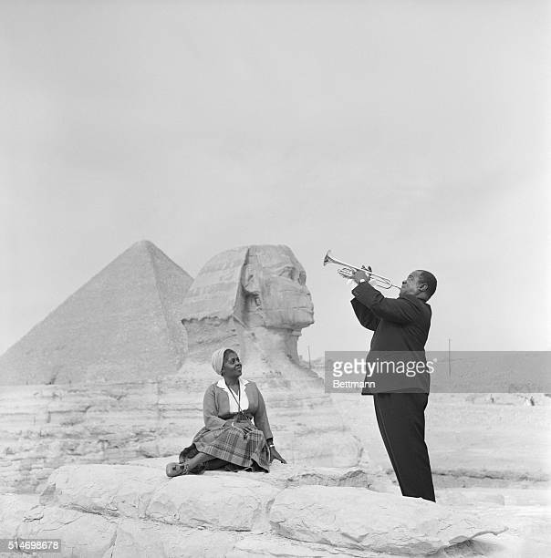 American jazz trumpeter Louis Armstrong plays the trumpet while his wife sits listening with the Sphinx and one of the pyramids behind her during a...