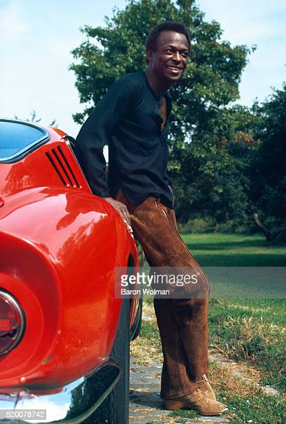 American jazz trumpeter Miles Davis leans on his Ferrari 275 GTB at his home in New York City October 1969