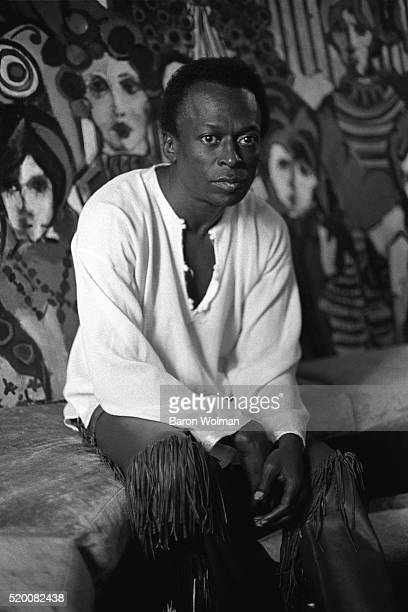 American jazz trumpeter Miles Davis sits in front of one of his fine art works at his home in New York City October 1969