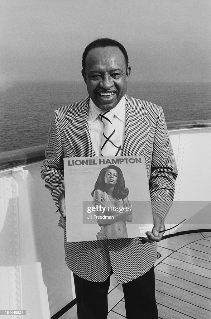 American jazz vibraphonist, pianist, and percussionist Lionel Hampton holds his album on board a jazz cruise, 1974.