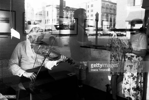 American jazz violinist and double bass player Johnny Frigo playing the violin in the window of a River North Art Gallery on Orleans St Chicago...