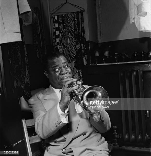 American jazzman Louis Armstrong plays trumpet in his dressing room before a show in March 1950 in New York