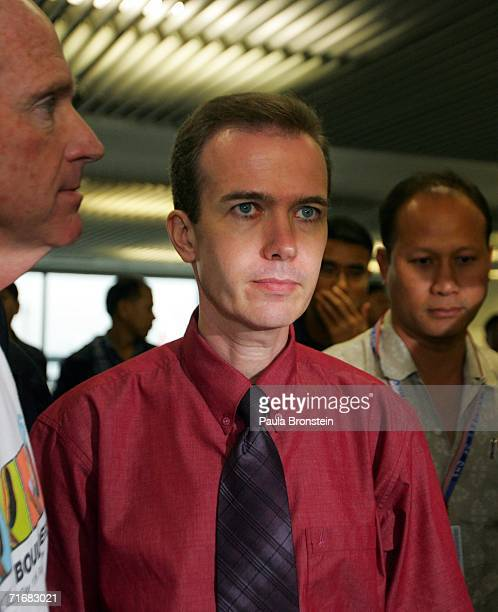 American John Mark Karr is escorted by US security officials as he arrives at Gate 46 for his flight to Los Angeles on Thai Airways at Bangkok...