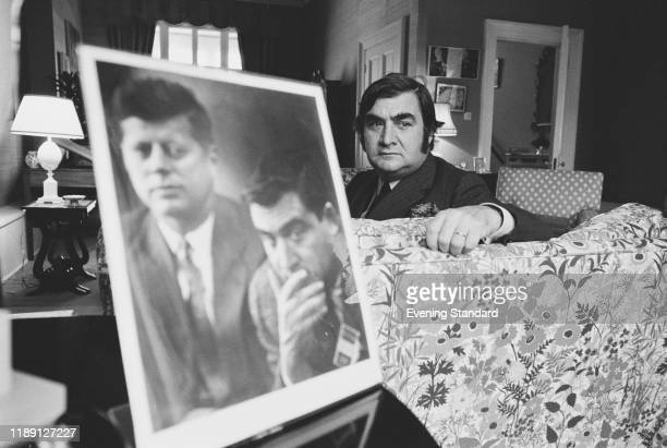American journalist and politician Pierre Salinger posed with a portrait of himself and President John F Kennedy in London on 14th November 1970....