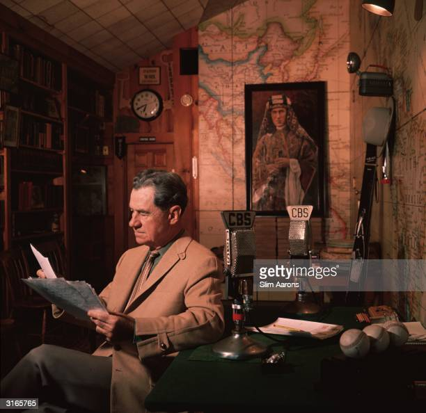 American journalist and radio broadcaster Lowell Thomas whose news stories made the British soldier T E Lawrence whose picture is on the wall behind...