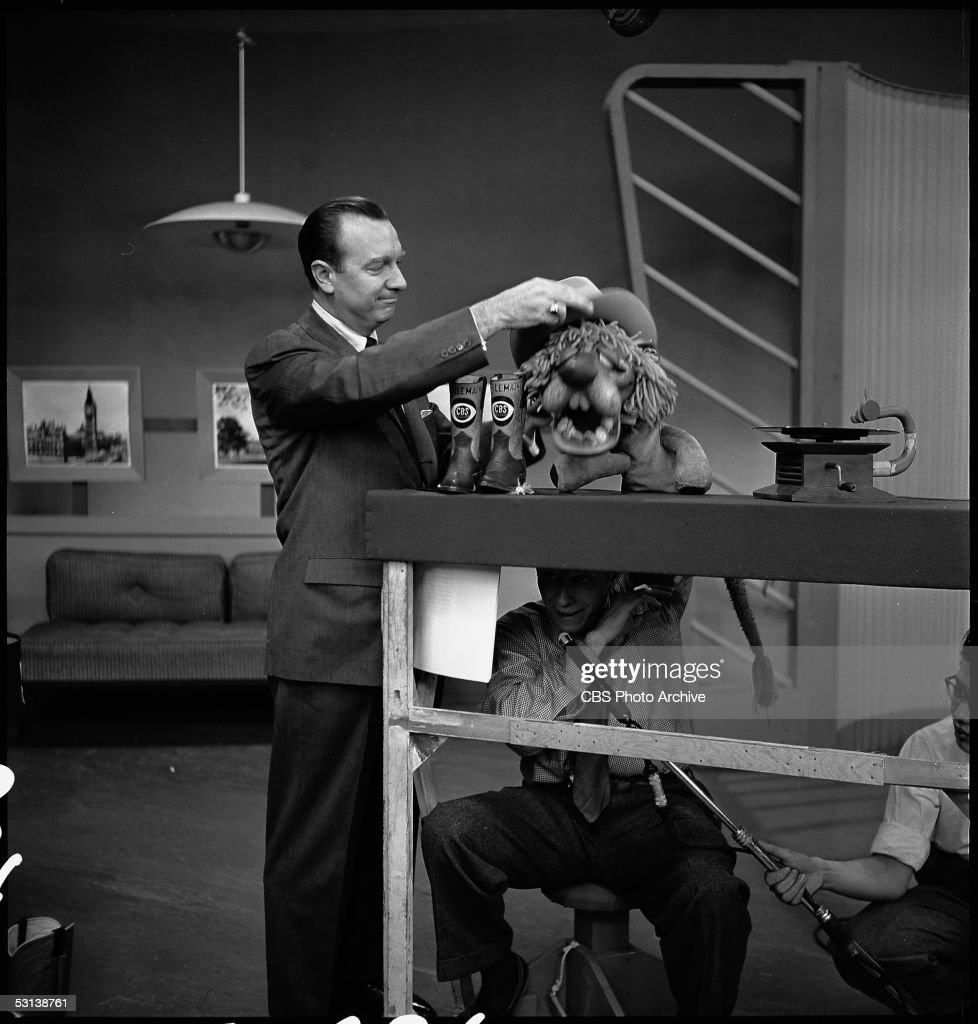 American journalist and television host Walter Cronkite (left) puts a cowboy hat on the head of Charlemagne the Lion (operated by puppeteer Bil Baird (1904 - 1987) (under table) on an episode of 'The Morning Show,' 1954. A pair of cowboy boots, with Charlemagne's name and the CBS logo, are on the table next to them. A boom operator, also under the table, holds Baird's microphone.