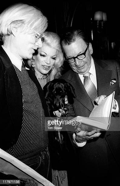 American journalist Earl Wilson shows a copy of his book 'Sinatra An Unauthorized Biography' to Pop artist Andy Warhol and an unidentified dog lover...