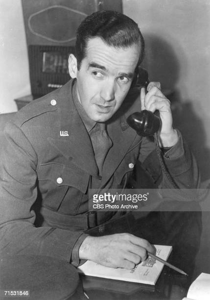 American journalist Edward R Murrow in a US military war correspondent's uniform talks on the phone as he prepares a report on World War II from...
