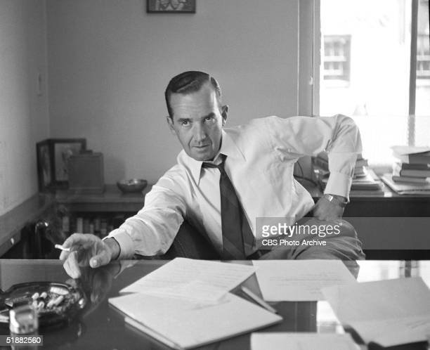 American journalist Edward R Murrow sits at a desk and smokes a cigarette with one hand on his hip July 24 1953