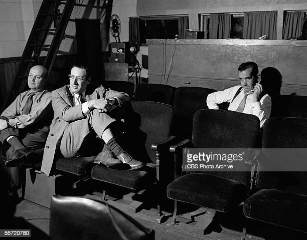 American journalist Edward R Murrow smokes a cigarette as he and producer Fred Friendly and an unidentified man sit in a screening room and watch...