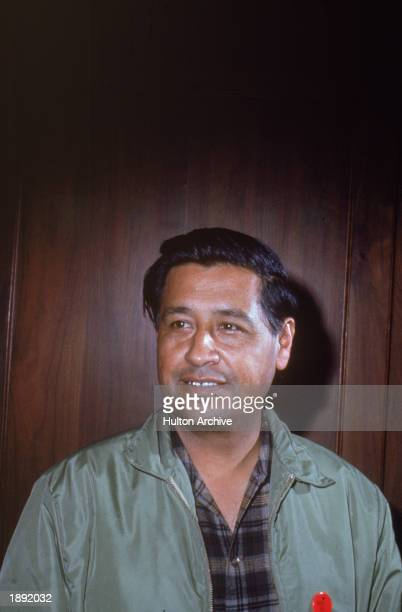 American labor leader Cesar Chavez smiles while standing in front of a wooden wall 1950s