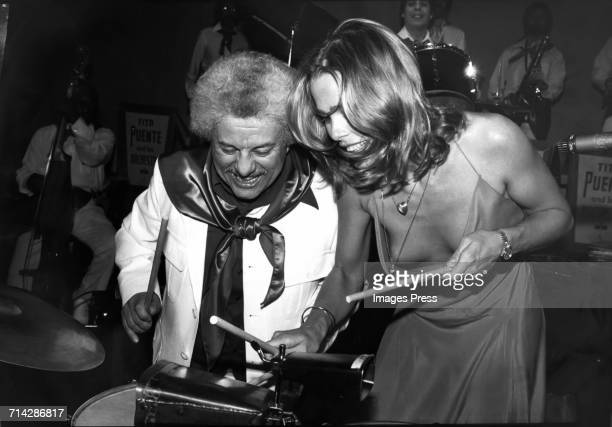 American Latin Jazz and Mambo musician Tito Puente , in a white jacket and scarf, is joined on the drums by actress and model Margaux Hemingway , in...