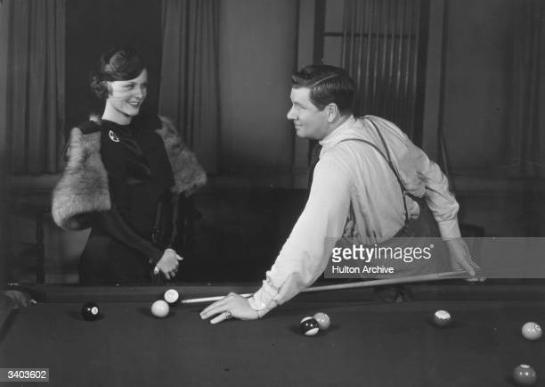 American leading lady Frances Dee talks to George Bancroft during a game of pool in a scene from the film 'Blood Money' directed by Rowland Brown for...