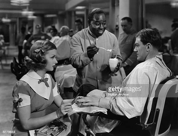 American leading lady Joan Bennett performs a manicure on Douglas Fowley while Fred 'Snowflake' Toomes offers him a milkshake in the Paramount comedy...